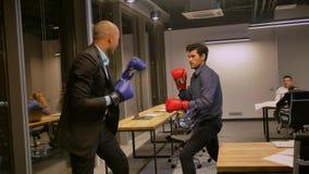 Twee concurrerende zakenlieden die met bokshandschoenen in collectief bureau vechten stock video