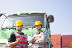 Twee containerarbeiders met vrachtwagen stock foto's