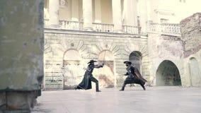 Twee cosplay musketiers de musketiers en de strijd op zwaarden stock footage