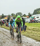 Twee Cyclsits op Cobbelstoned-Road in de Regen Stock Foto's