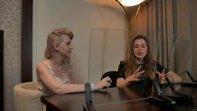 Twee dames bekijken twee transparante geplaatst en vertoningen die bespreken stock videobeelden