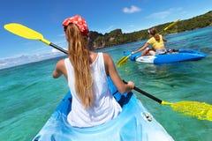 Twee dames op zee kajaks die in blauwe lagune lopen Stock Fotografie