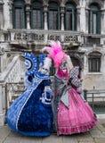 Twee dames ventilators houden en hand geschilderde maskers dragen en overladen blauwe en roze kostuums die in Venetië C stock foto's