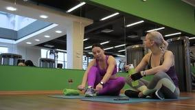 Twee dames zitten op de matten in de geschiktheidsclub en spreken vóór de klasse stock footage