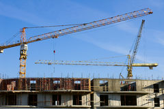Twee de bouwkranen en blauwe hemel Royalty-vrije Stock Afbeeldingen