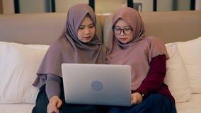 Twee de jonge moslimvideo van het vrouwenhorloge op laptop in de slaapkamer stock videobeelden