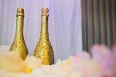 Twee decoratieve gouden flessen luxechampagne met copyspace voor uw Nieuwjaar, Kerstmis of huwelijksgroet of stock foto