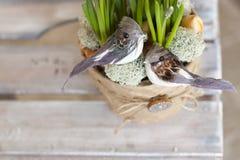 Twee decoratieve vogels zitten in een bloempot met bloemen stock afbeelding
