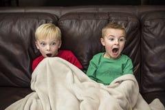 Twee deden schrikken kleine jongens die op een laag zitten op TV letten royalty-vrije stock afbeelding