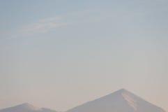 Twee die bergpieken met sneeuw worden behandeld Stock Fotografie