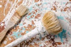 Twee die borstels op een houtvezelplaat met verf wordt bevlekt royalty-vrije stock afbeelding