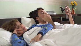 Twee die broers liggen in met algemeen wordt behandeld en vermoeid bed beide geeuw Broersverhouding stock video