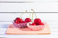 Twee die cupcakevoeringen met kersen worden gevuld royalty-vrije stock foto's