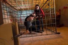 Twee die Halloween-slachtoffers in een metaalkooi worden gevangengenomen, jongen die hallo trekken stock fotografie
