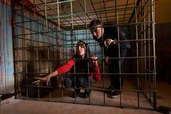Twee die Halloween-slachtoffers in een metaalkooi worden gevangengenomen, meisje die h trekken stock afbeeldingen
