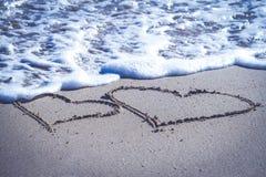 Twee die harten op het zand van het strand en de blauwe overzeese golven met schuim worden getrokken Royalty-vrije Stock Foto