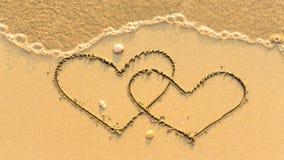 Twee die harten op het zandstrand worden getrokken met de zachte golf Royalty-vrije Stock Foto