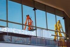 Twee die havenkranen in venster worden weerspiegeld stock afbeelding