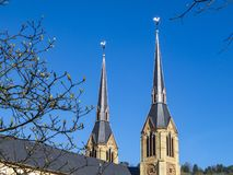 Twee die kerkspitsen door weerhanen tegen een duidelijke blauwe hemel en een ontluikende boom van Maart worden bedekt vertakt zic stock afbeeldingen