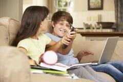 Twee die Kinderen door Televisie worden afgeleid terwijl het proberen om met Thuiswerk te doen stock foto
