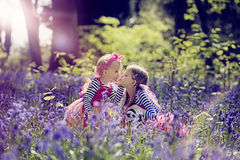 Twee die kinderen in een hout met de lenteklokjes wordt gevuld Stock Afbeelding