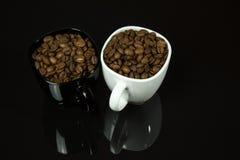 Twee die koppen met koffiebonen worden gevuld op een zwarte achtergrond met p Stock Foto's