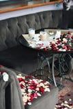 Twee die koppen van koffie op een lijst met bloemblaadjes wordt uitgestrooid De kerel bekende enkel zijn liefde aan zijn meisje Stock Foto