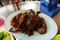 Twee die krabben in zwarte pepersaus worden gekookt op een witte plaat wordt gediend Royalty-vrije Stock Foto
