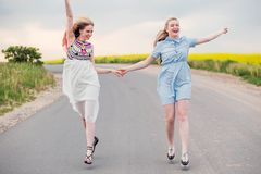 Twee die meisjes op de wegholding handen en het lachen in werking worden gesteld royalty-vrije stock foto