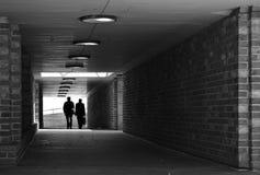 Twee die mensen tegen een helder licht worden gesilhouetteerd die door een tunnel met bakstenen muren naar de zwart-wit camera lo royalty-vrije stock fotografie