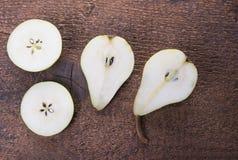 Twee die perenfruit in de helft op bruine houten achtergrond wordt gesneden Royalty-vrije Stock Foto