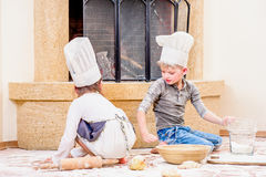 Twee die siblings - jongen en meisje - in chef-kok` s hoeden dichtbij de open haardzitting op de keukenvloer met bloem wordt bevu stock fotografie