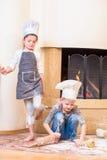 Twee die siblings - jongen en meisje - in chef-kok` s hoeden dichtbij de open haardzitting op de keukenvloer met bloem wordt bevu stock foto