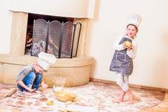 Twee die siblings - jongen en meisje - in chef-kok` s hoeden dichtbij de open haardzitting op de keukenvloer met bloem wordt bevu royalty-vrije stock afbeelding