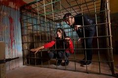 Twee die slachtoffers in een metaalkooi worden gevangengenomen, meisje die haar handth trekken stock foto