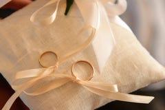 Twee die trouwringen op een kussen met lint wordt gebonden Stock Foto's