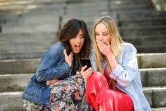 Twee die vrouwen worden verbaasd door wat zij op hun slimme telefoon zien Stock Foto