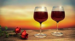 Twee die wijnglazen met rode wijn met twee rode rozen tijdens zonsondergang worden gevuld Royalty-vrije Stock Afbeeldingen