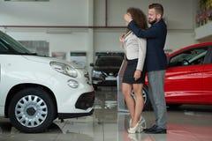 Twee die zich in de man van het autocentrum holdingshanden bevinden op het oog van de vrouw royalty-vrije stock foto
