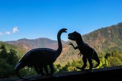 Twee dinosaurussen - een brontosaurus en t rex - confronteren elkaar in silhouet met uit nadrukbergen in de afstand stock fotografie