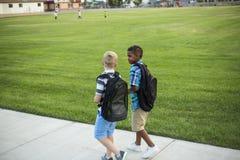 Twee diverse schooljonge geitjes die en samen op de manier aan school lopen spreken royalty-vrije stock afbeelding