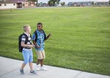 Twee diverse schooljonge geitjes die naar huis samen na school lopen stock fotografie