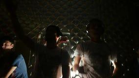 Twee DJ achter de dekken geven geboorte aan een partij die met licht met hoofdtelefoons dansen stock videobeelden