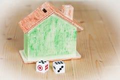 Twee dobbelen en huisvesten bank op houten Stock Afbeeldingen