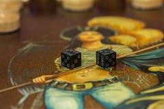 Twee dobbelen en spaanders op de backgammonlijst Stock Afbeelding
