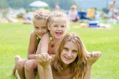 Twee dochters leunen op de moeders achterover, het hete de zomerdag ontspannen op de groene gazon mooie stranden Royalty-vrije Stock Afbeeldingen