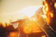 Twee document vliegtuigen in handen die elkaar bij zonsondergang bekijken Jongeren die document vliegtuigen, liefde, relatiesconc Stock Afbeelding