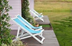 Twee doen leunen stoelen op dok die een groen meer onder ogen zien stock foto