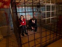 Twee doen schrikken die Halloween-slachtoffers in een metaalkooi worden gevangengenomen royalty-vrije stock afbeeldingen