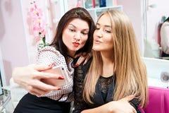 Twee donkerbruine meisjes en een blonde maken een selfie in een schoonheidssalon stock fotografie